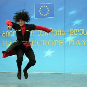 Georgian dancer against backdrop of EU flag