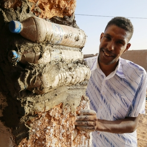 Tateh Lehbib shows how to build an ecological house from waste plastic bottles filled with sand. The circular houses, built in the Tindouf refugee camp, are resistant to wind and heavy rains and offer good protection against the harshness of the Algerian desert.