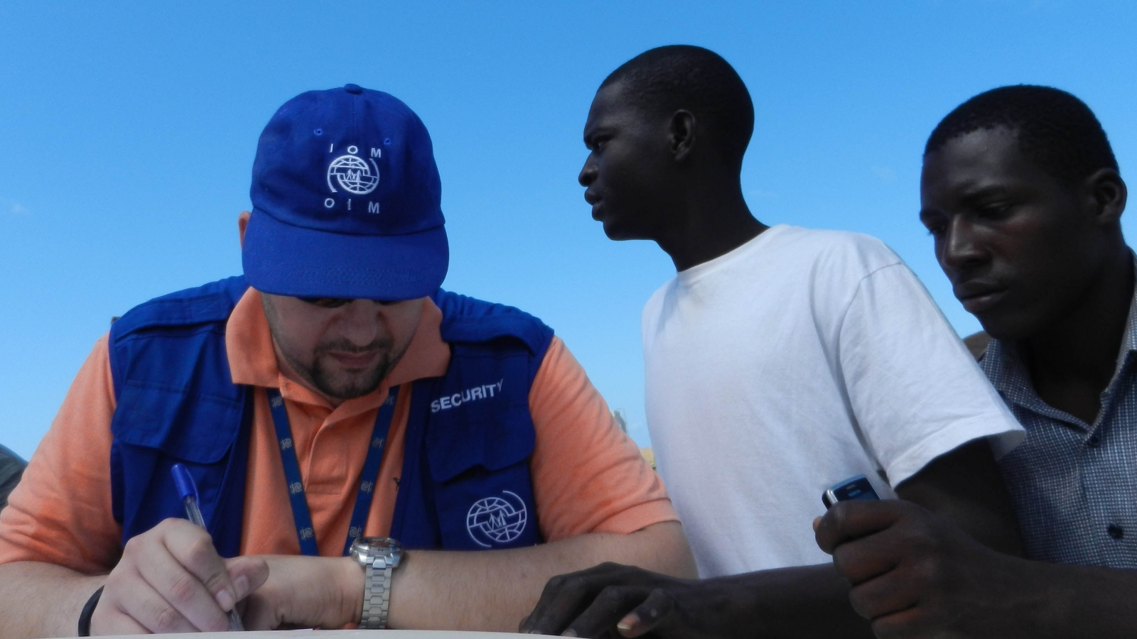 An IOM official taking migrants' names at Janzour port, near Tripoli