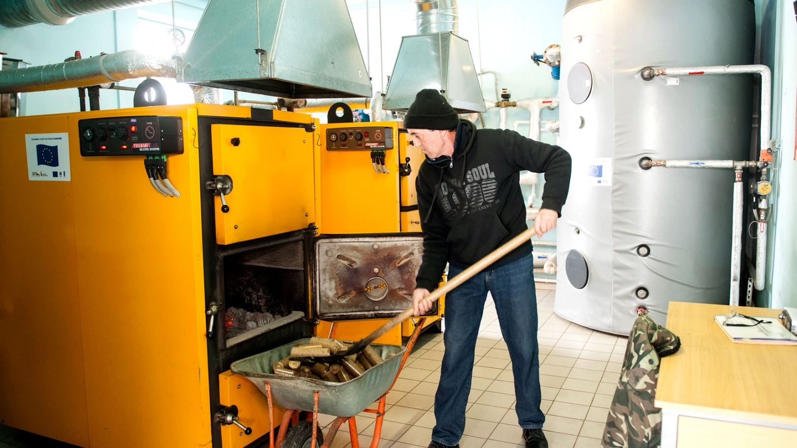 Vasilii Gaina throws pellets into a biomass boiler.