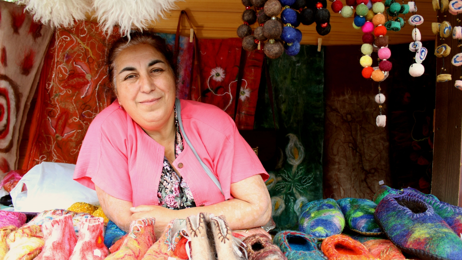 "Feltmaster Lali Sadaghashvili inside of her rack selling felt slippers made at her worksop ""Nerbi"" at old town Mtskheta"