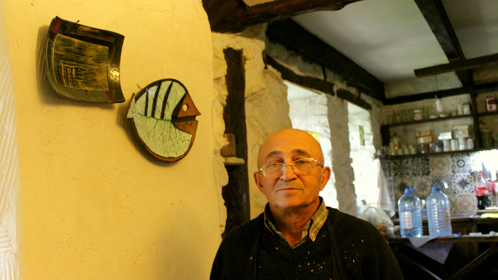 Ceramist Otar Sharabidze his pottery works on the background in his house in Tetritskaro