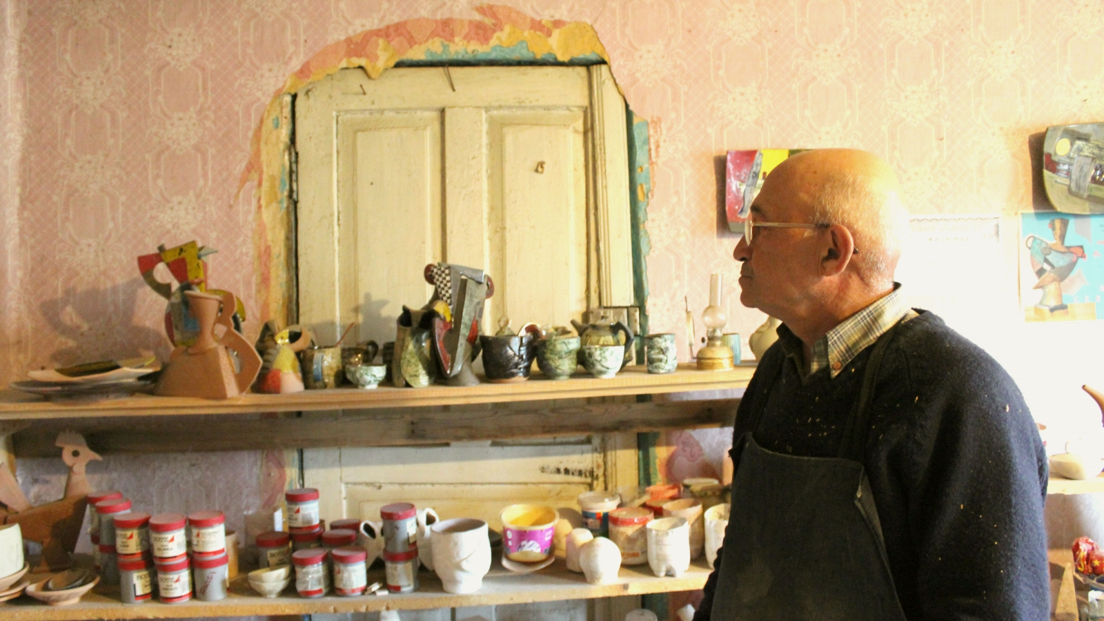 Otar Sharabidze looking at his ceramic works