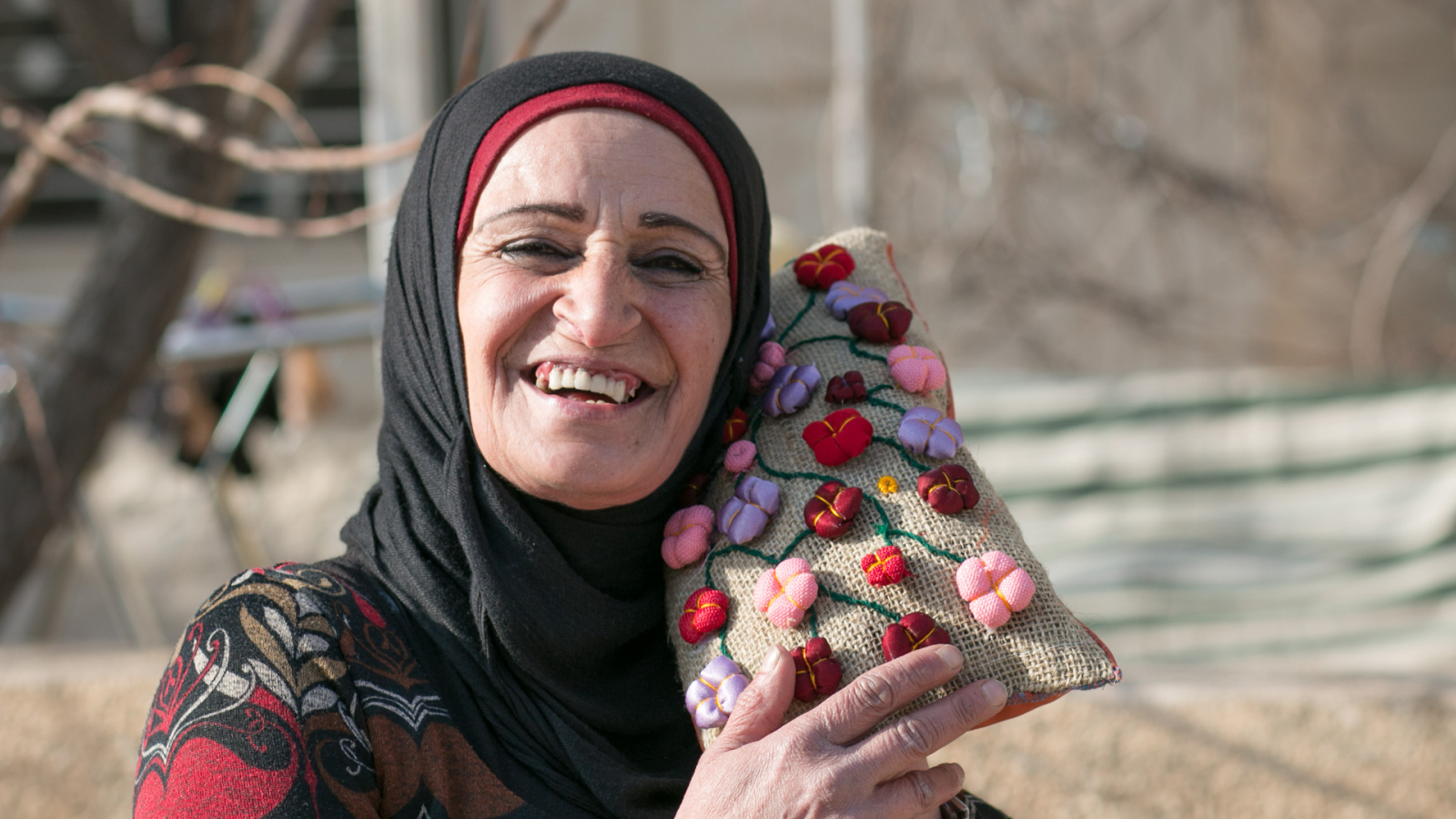 Souhayla beneficiary of the EU-funded project Dawric posing with one of her creations, Douris, Lebanon